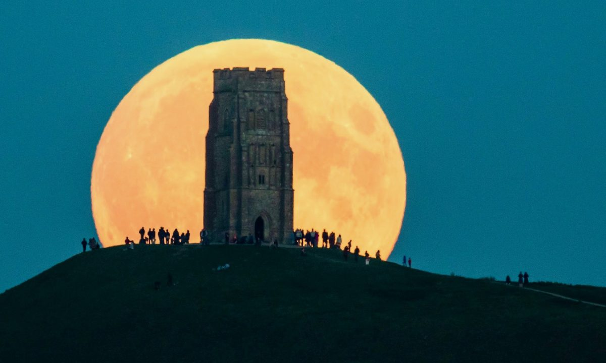 A supermoon rises behind Glastonbury Tor, Somerset in 2015. (Credit: Matt Cardy/Getty Images)